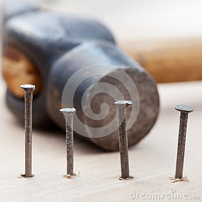 Hammer and nails into wooden plank