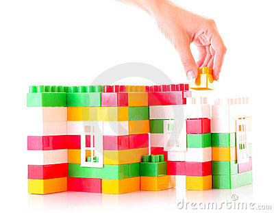 Hand add toy brick to toy building