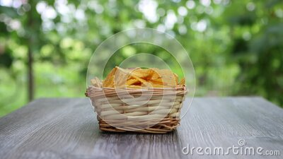 Hand of adult female taking potato chips from wickered bowl in garden stock footage