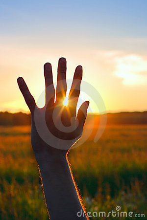 Hand against sunset