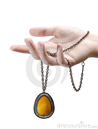 A hand with an amber pendant  isolated