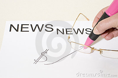 Hand with ballpoint on news board