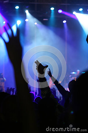 Hand with beer glass in the air in a concert
