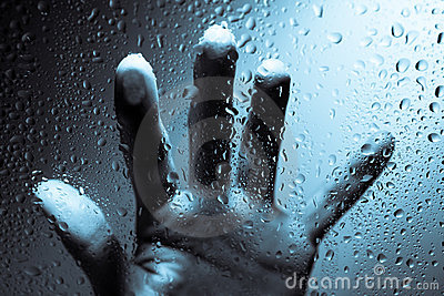 Hand behind wet window