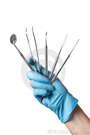 Hand in blue glove holding dental tools isolated