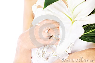 Hand of a bride with ring and flowers