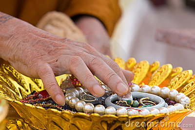 Hand of Buddhist monk painting religious symbols