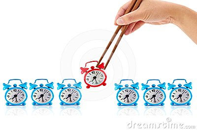 Hand with chopsticks and  alarm clock