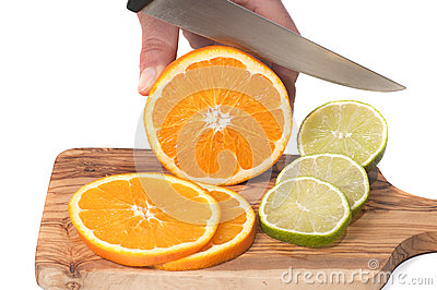 Hand cutting orange and lime slices on a wooden board, isolated en white