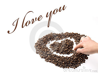 Hand designing a heart with coffee beans