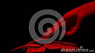 Hand die die dollar van stapel nemen door rood licht, de bloedige beloning van de geldmisdaad wordt verlicht stock footage