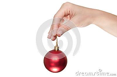 Hand, die eine rote Weihnachtskugel anhält