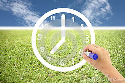 Hand is drawing a clock on lawns and blue sky.