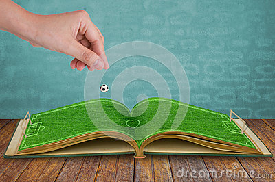Hand drop football down to green grass