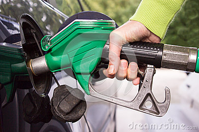 Hand filling the car tank with gasoline