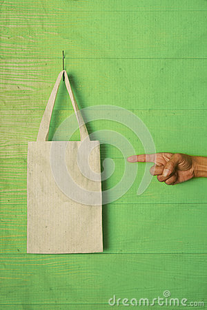 Hand and finger pointing to clothes bag on green