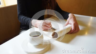 Hand of a girl draws in sketchbook with a pencil in a cafe, a cup of coffee on the table, long Travelling shot stock video footage