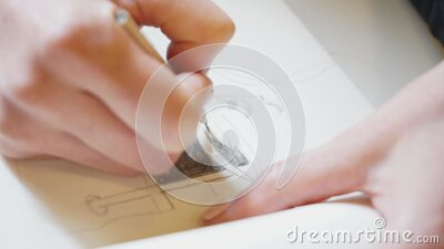 Hand of a girl draws in sketchbook with a pencil close up stock video footage