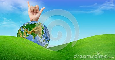 A hand with a globe and a grass field