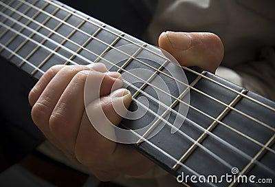 Hand on guitar fingerboard