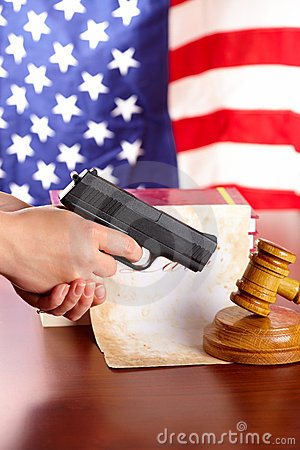 Hand with gun and judges gavel - Vertical