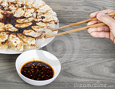 Hand held chopsticks reaching for Dumplings