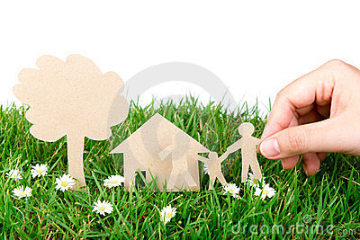 Hand hold paper cut  of family over green grass.