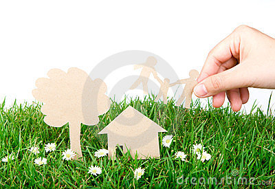 Hand hold paper cut of family over green grass