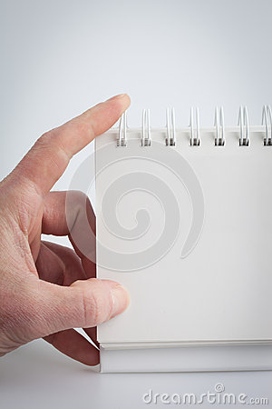 Hand holding a blank note pad