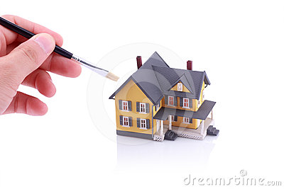 Hand holding brush for painting house