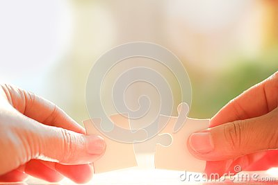 Hand holding and connecting jigsaw puzzles Stock Photo