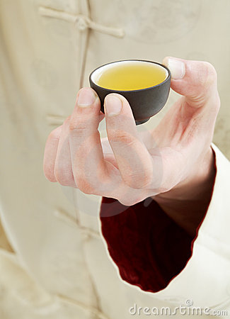 Hand holding cup of green tea