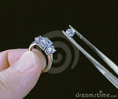 Hand holding diamond ring and stone with tweezers