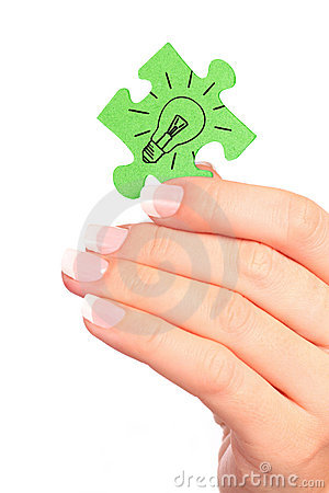 Hand holding drawn light bulb on puzzle