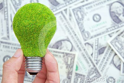 Hand holding eco light bulb on dollars background