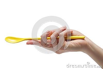 Hand holding an empty teaspoon