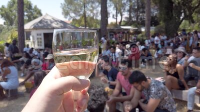 Hand holding a glass of white wine in Fourways Farmers Market with people socializing, Johannesburg, South Africa. Johannesburg, South Africa - October 2019 stock video footage
