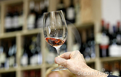 Hand holding glass of wine for tasting