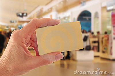 Hand Holding Gold Credit Card in Shopping Mall