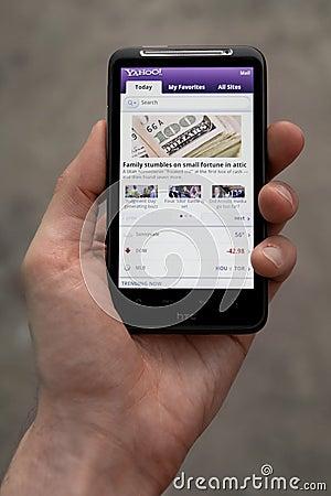 Hand holding HTC Desire HD showing Yahoo news