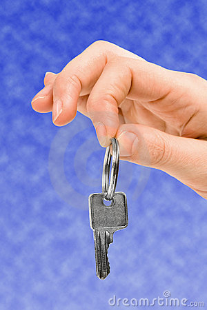 Hand holding key over blue sky