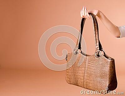 Hand holding leather handbag on the beige background