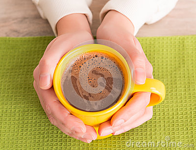 Hand holding a mug with coffee