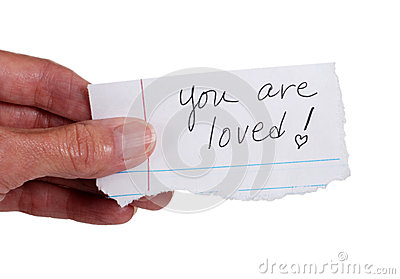 Hand holding note that reads  You Are Loved