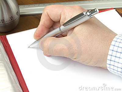 Hand holding a pen and sheet of a paper laying on