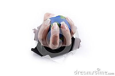 Hand holding planet thru a hole