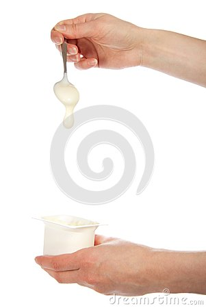 The hand holding a spoon with yogurt
