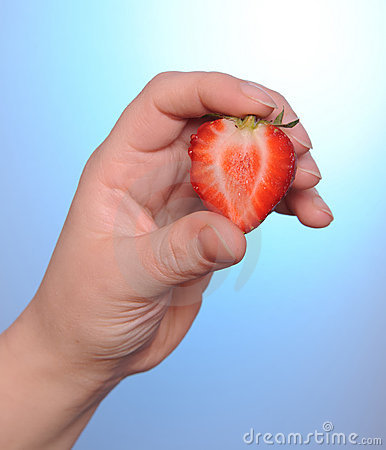 Hand holding a strawberry. Love concept