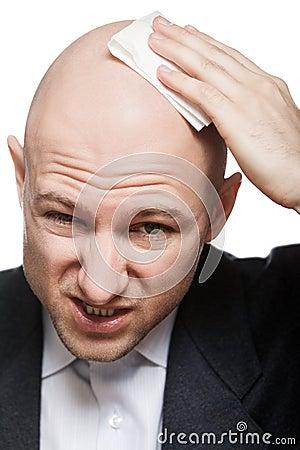 Hand holding tissue drying bald sweat head