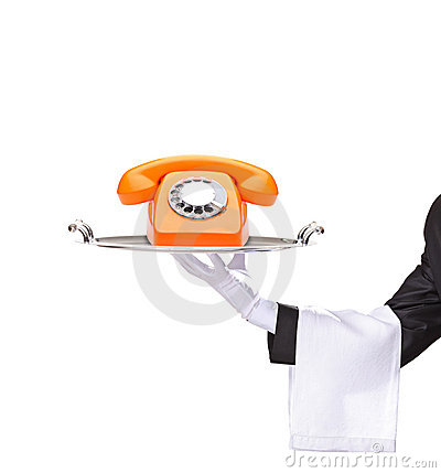 Hand holding a tray with an orange telephone